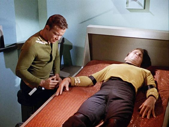 """LOS ANGELES - OCTOBER 6: William Shatner, as split versions of Captain James T. Kirk in STAR TREK: THE ORIGINAL SERIES episode, """"The Enemy Within."""" Season 1, episode 5. He is seen here as the good self, (approaching at left), and the evil version (lying down, in sick bay). Original air date is October 6, 1966. Image is a screen grab. (Photo by CBS via Getty Images) *** Local Caption *** William Shatner"""