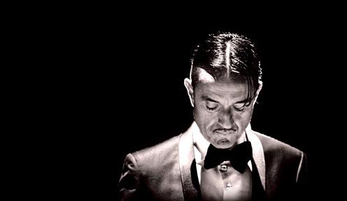 Ingessato in abiti e acconciatura eleganti, un ricco e autorevole banchiere (Giulio Base) festeggia il compleanno nella sua lussuosa dimora. Con lui, un solo commensale (Paolo Fosso) che, domanda dopo […]